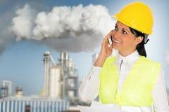 Glimlachende dameingenieur die op de telefoon en de fabriek in Th spreken Royalty-vrije Stock Afbeeldingen
