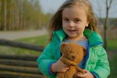 Glimlachende de holdingsteddybeer van het babymeisje in openlucht stock fotografie