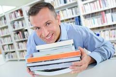 Glimlachende de stapelboeken van de mensenholding Royalty-vrije Stock Afbeeldingen