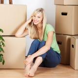 Glimlachende die vrouw door kartonkartons wordt omringd Stock Afbeeldingen