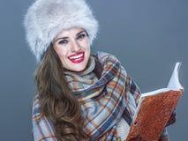 Glimlachende in die vrouw op koude blauwe achtergrond met boek wordt geïsoleerd Stock Fotografie