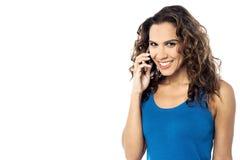Glimlachende die vrouw op telefoon, over een wit wordt geïsoleerd Royalty-vrije Stock Afbeeldingen