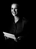 Glimlachende die vrouw op zwarte achtergrond wordt geïsoleerd die tabletpc met behulp van Royalty-vrije Stock Foto