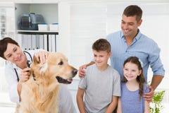Glimlachende dierenarts die een hond met zijn eigenaars onderzoeken Royalty-vrije Stock Foto's