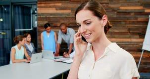 Glimlachende directeur die op mobiele telefoon spreken stock footage