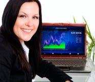 Glimlachende donkerbruine onderneemster in bureau met laptop stock foto