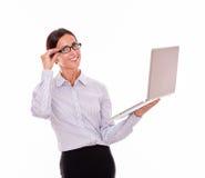 Glimlachende donkerbruine onderneemster met laptop Royalty-vrije Stock Foto's