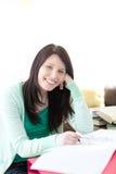 Glimlachende donkerbruine student die haar thuiswerk doet Stock Fotografie