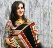 Glimlachende donkerbruine vrouw die de harmonika spelen royalty-vrije stock afbeelding