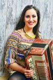 Glimlachende donkerbruine vrouw die de harmonika spelen stock afbeelding
