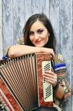 Glimlachende donkerbruine vrouw die de harmonika spelen stock afbeeldingen