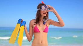 Glimlachende donkerbruine vrouw die een snorkelend materiaal houden stock videobeelden