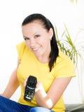 Glimlachende donkerbruine vrouw die op TV let Royalty-vrije Stock Afbeeldingen