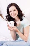 Glimlachende donkerbruine vrouw die zwarte koffie drinkt Stock Fotografie