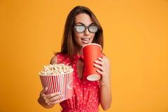 Glimlachende donkerbruine vrouw in kleding en oogglazen die voorbereidingen treffen te letten op Stock Afbeeldingen