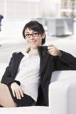 Glimlachende donkerbruine vrouw op bank op kantoor Stock Afbeeldingen