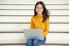 Glimlachende donkerbruine vrouw in sweaterzitting op de vloer met laptop computer en het kijken weg over grijze achtergrond royalty-vrije stock foto