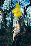 Glimlachende elegante maniervrouw met ballons in bos royalty-vrije stock afbeelding