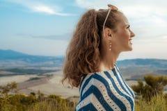 Glimlachende elegante toeristenvrouw die afstand onderzoeken royalty-vrije stock afbeelding