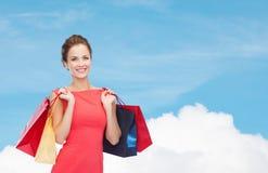 Glimlachende elegante vrouw in kleding met het winkelen zakken Stock Foto