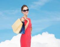 Glimlachende elegante vrouw in kleding met het winkelen zakken Stock Foto's