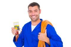 Glimlachende elektricien met gerolde draad en multimeter stock fotografie
