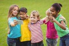 Glimlachende en klasgenoten die selfies stellen nemen stock afbeelding
