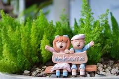 Glimlachende en lachende jongen en meisjeskleipop met welkom woord Stock Foto