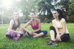 Glimlachende en vrolijke vrienden op gras in park na het lopen Royalty-vrije Stock Foto