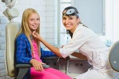 Glimlachende Ent arts of Otolaryngoloog die een jong geitje onderzoeken Stock Afbeelding