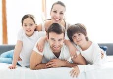 Glimlachende familie in bed Stock Fotografie