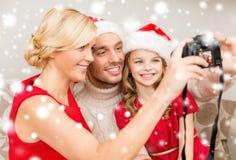 Glimlachende familie in de hoeden die van de santahelper beeld nemen Stock Foto
