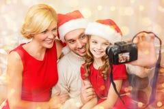 Glimlachende familie in de hoeden die van de santahelper beeld nemen Royalty-vrije Stock Foto's