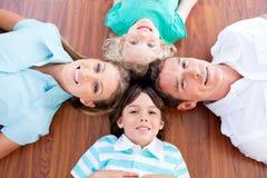 Glimlachende familie die in cirkel op de vloer ligt royalty-vrije stock afbeeldingen