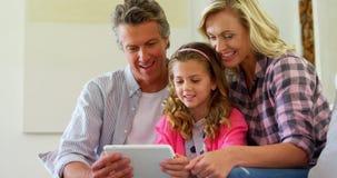 Glimlachende familie die digitale tablet samen in woonkamer 4k gebruiken stock videobeelden