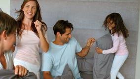 Glimlachende familie die een hoofdkussenstrijd hebben stock videobeelden