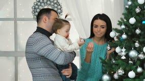 Glimlachende familie die een Kerstboom in de woonkamer verfraaien stock footage