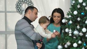 Glimlachende familie die een Kerstboom in de woonkamer verfraaien stock videobeelden