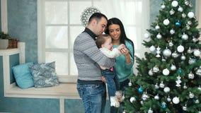 Glimlachende familie die een Kerstboom in de woonkamer verfraaien stock video