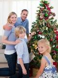 Glimlachende familie die een Kerstboom verfraait Stock Afbeelding