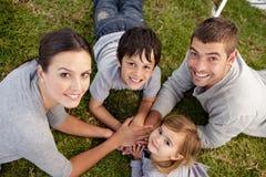 Glimlachende familie die in een park ligt Royalty-vrije Stock Foto