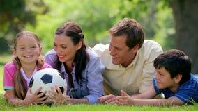Glimlachende familie die een voetbalbal proberen te vangen stock videobeelden
