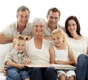 Glimlachende familie die fotoalbum waarneemt Royalty-vrije Stock Foto's