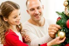 Glimlachende familie die Kerstmisboom thuis verfraaien Stock Afbeelding