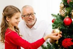 Glimlachende familie die Kerstmisboom thuis verfraaien Stock Afbeeldingen