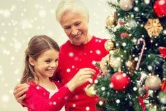 Glimlachende familie die Kerstmisboom thuis verfraaien Royalty-vrije Stock Afbeeldingen