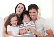 Glimlachende familie die laptop in de woonkamer met behulp van Royalty-vrije Stock Foto's