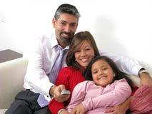 Glimlachende familie die op TV in de woonkamer let Stock Fotografie