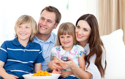 Glimlachende familie die op TV let Royalty-vrije Stock Afbeeldingen