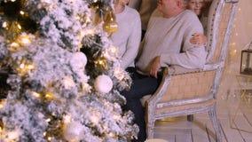 Glimlachende familie die pret hebben dichtbij decoratieve Nieuwjaarboom bij vakantie in comfortabel huis stock video